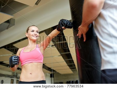 sport, fitness, lifestyle and people concept - smiling woman with personal trainer boxing punching bag in gym
