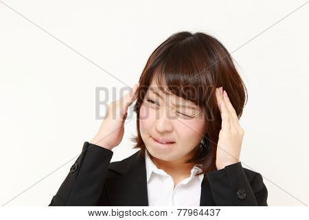 portrait of young Japanese businesswoman suffers from headache poster