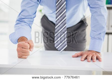 Businessmans fist clenched over desk in his office