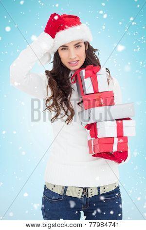 Stressed brunnette in santa hat holding gifts against blue background with vignette