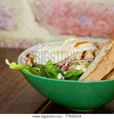 Fried egg on a plate with ceaser salad