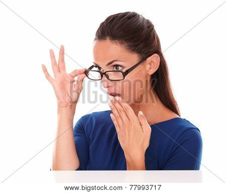 Shy girl looking embarrassed with hand on mouth looking over glasses in white background - copyspace poster