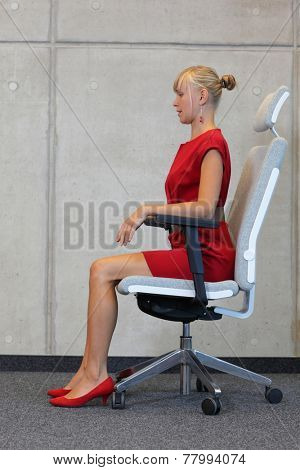 caucasian woman in red dress sitting on office armchair in proper position