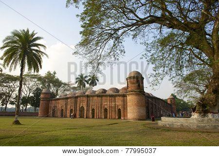 Unidentified people explore Shat Gombuj Mosque, Bagerhat, Bangladesh.
