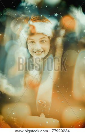 Festive litte girl decorating christmas tree against candle burning against festive background