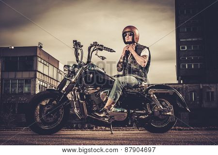 Tattooed biker and his bobber style motorcycle on a city streets