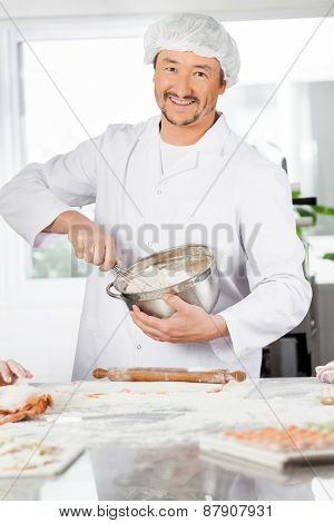 Portrait of happy male chef mixing batter in bowl to prepare ravioli pasta in commercial kitchen