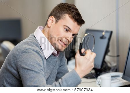 Frustrated male customer service representative holding headphones in office
