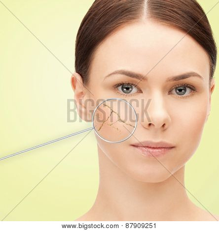 health, people, skin care and beauty concept - beautiful young woman face with dry dehydrated skin and magnifying glass over green background