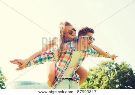 holidays, vacation, love and friendship concept - smiling couple having fun in park