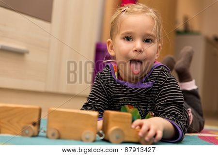 Cheeky Little Girl Is Playing With A Wooden Toy