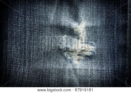 Frayed or torn jean fabric.