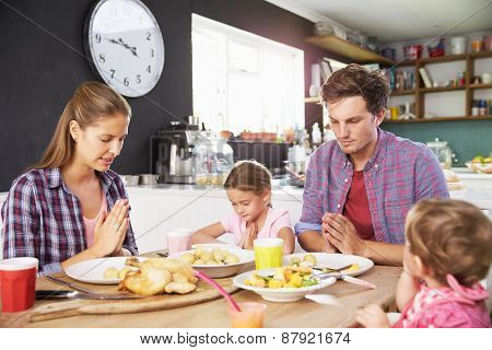 Family Saying Prayer Before Eating Meal In Kitchen Together