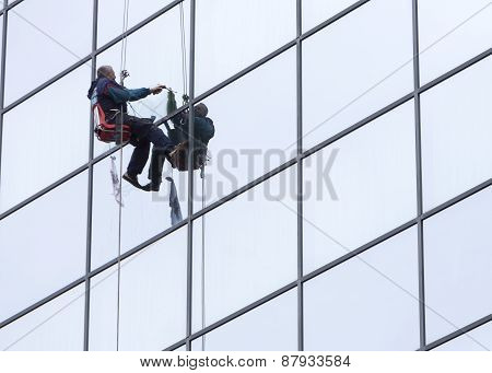 Sanitation Worker Cleaning Glass Facade Hotel