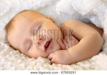 Smiling Sleeping Newborn Baby Girl Wrapped In White Blanket