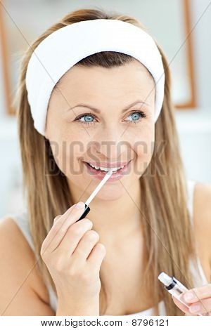 Glowing Woman Applying Gloss On Her Lips In The Bathroom