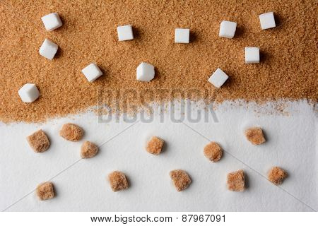 White and brown sugar contrast. White sugar cubes on raw brown turbinado granules and raw brown sugar lumps on white granulated sugar.