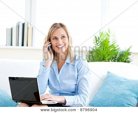 Smiling Businesswoman Talking On Phone And Using Her Laptop Sitting On A Sofa