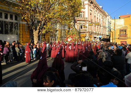 La Paz Bolivia - 29 March 2013: Holy Thursday traditional Easter procession in Spanish colonial Semana Santa style along Plaza Murillo. Penitents with traditional red hoods carry a statue virgin mary mother of jesus christ.