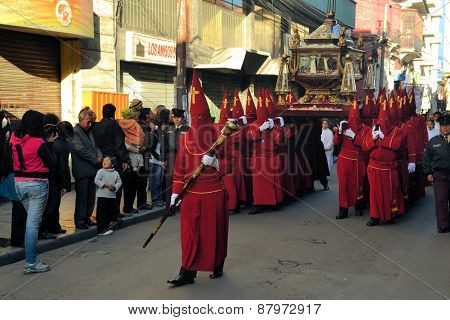 La Paz Bolivia - 29 March 2013: Holy Thursday traditional Easter procession in Spanish colonial Semana Santa style along Plaza Murillo. Penitents with traditional red hoods carry a statue of jesus christ the savior.
