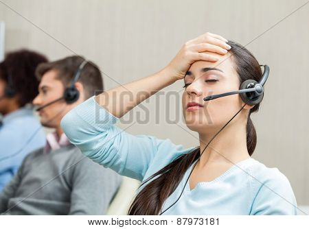 Tired female customer service agent with colleagues in background at call center