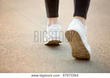 Female feet in white sneakers running on concrete jogger practicing close-up. Healthy active lifestyle concepts copy space poster