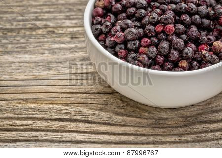 freeze dried elderberries in white, ceramic bowl against grained wood