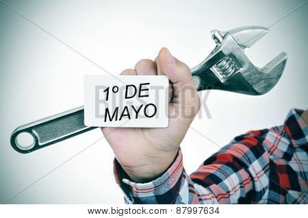 closeup of the hand of a young caucasian worker man with an adjustable wrench and a signboard with the text 1o de mayo, may day written in spanish