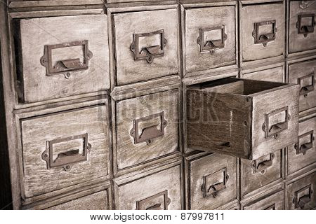 a big cabinet with one drawer left open poster