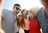 tourism, travel, people, leisure and technology concept - group of happy laughing teenage friends taking selfie outdoors poster