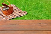 Empty Wooden Picnic Tabletop Close-up. Picnic Basket and Blanket On The Summer Lawn In The Background. poster