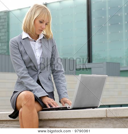 A young blond woman is working on the laptop