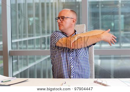 middle age balding man  stretching arm in his office  - short break for exercise