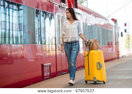 Young happy woman with luggage at a train station