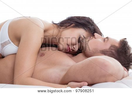 Loving pair tenderly embracing while lying in bed