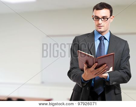 Businessman reading his agenda in his office poster