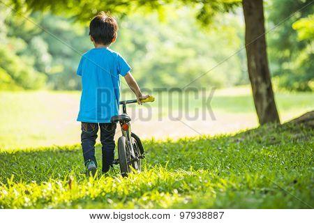 Little toddler boy repairing his first bike