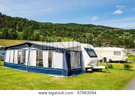 Modern caravan with caravan tent at campsite in Norway on a sunny summer day. poster