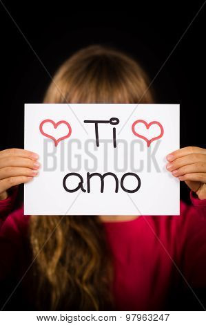 Studio shot of child holding a sign with Italian words Ti Amo - I Love You poster