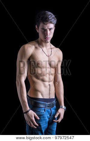 Handsome, fit shirtless young man in jeans isolated on black