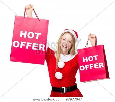 Woman with christmas party dress hold up with shopping bag and showing hot offer