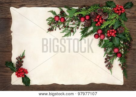 Christmas background floral border with red bauble decorations, holly, ivy, fir, cedar cypress and pine cones on parchment paper over old oak wood.