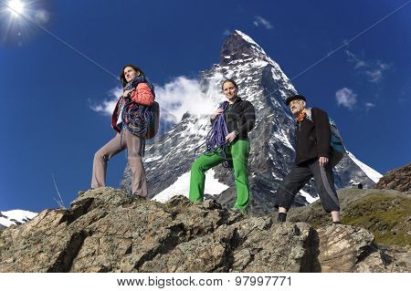Team of climbers walks against alpine background Farther and daughters walk on the mountain ridge. High alpine landscape on the background poster