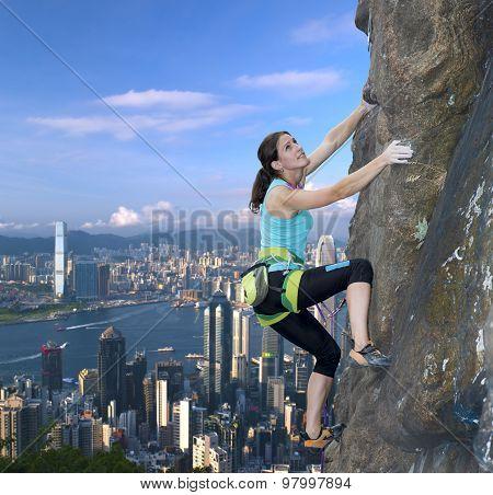 Female rock climber over the city skyline