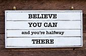 Believe You Can and You're Halfway There Inspirational message written on vintage wooden board. Motivational concept image poster