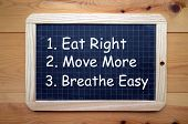 Health and Fitness advice to Eat Right, Move More and Breathe Easy in white text on a slate blackboard poster