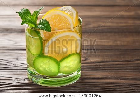 cool drink with lemon and mint on a wooden background