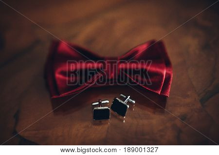 Stylish Red Bow Tie And Cuff Links On Wooden Table, Groom Getting Ready In Morning Before Wedding. G