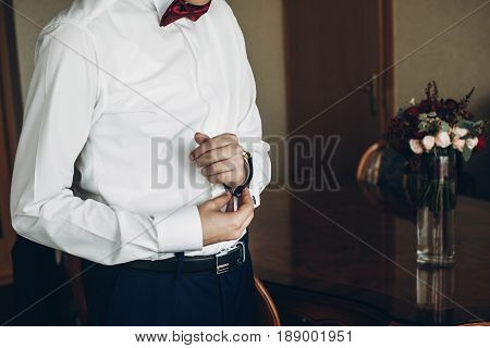 Groom Getting Ready In The Morning Before Wedding Ceremony, Putting On Cuff Links On Shirt.