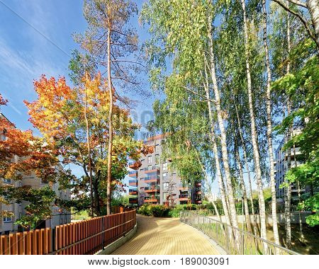 Vilnius, Lithuania - September 30, 3016: Birch trees and Modern glass residential apartment building. And outdoor facilities.